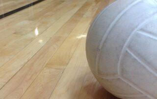 Pallone bianco da pallavolo appoggiato su una riga del campo